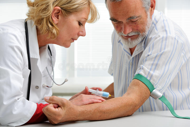 Doctor with syringe is taking blood for test stock photos