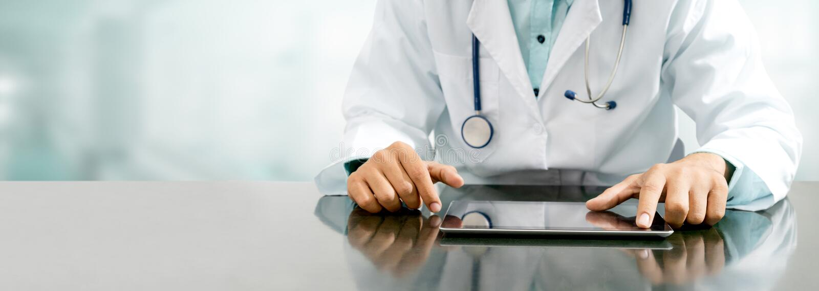 Doctor with tablet computer at hospital office. Male doctor sitting at table with tablet computer in hospital office. Medical healthcare staff and doctor service stock photography