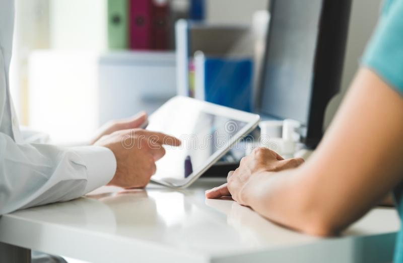 Doctor with tablet and patient having a discussion, meeting and appointment in hospital office room. stock photo
