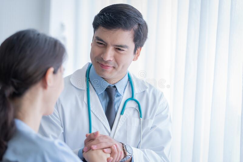 A doctor take care of sick patient woman at the hospital or medical clinic royalty free stock photo