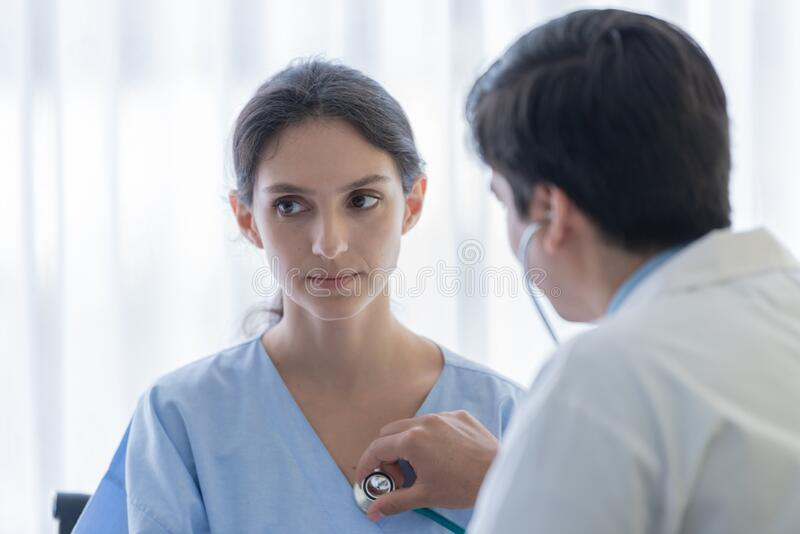 A doctor take care of sick patient woman at the hospital or medical clinic stock photography