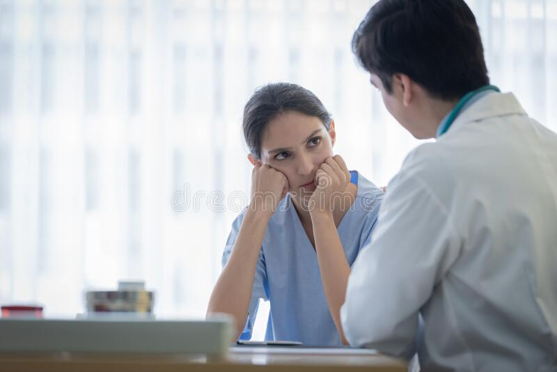 A doctor takes care of a sick patient woman with sadness and unhappiness at the hospital or medical clinic royalty free stock image