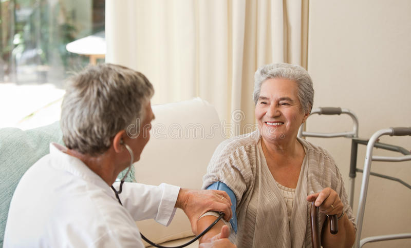 Doctor taking the blood pressure of his patient stock images