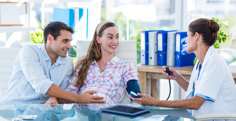 Doctor taking the blood pressure of a pregnant patient with her husband. In an examination room stock photos