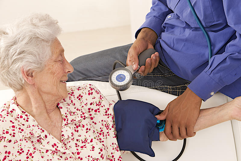 Doctor taking blood pressure to an elderly patient at home stock photo