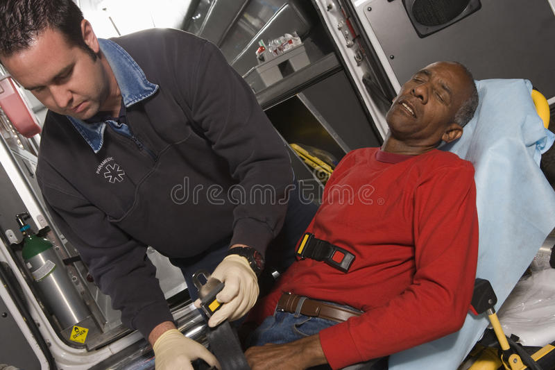 Doctor Taking Care Of A Senior Man. Male EMT professional taking care of a senior men inside ambulance royalty free stock photos