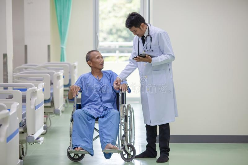 The doctor is taking care of senior patient in wheelchair royalty free stock images