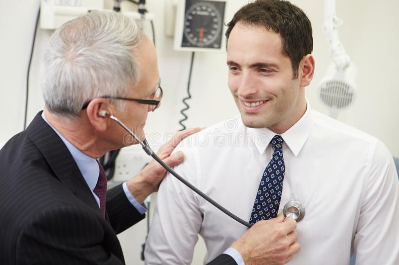 Doctor Taking Male Patient's Blood Pressure In Hospital stock image