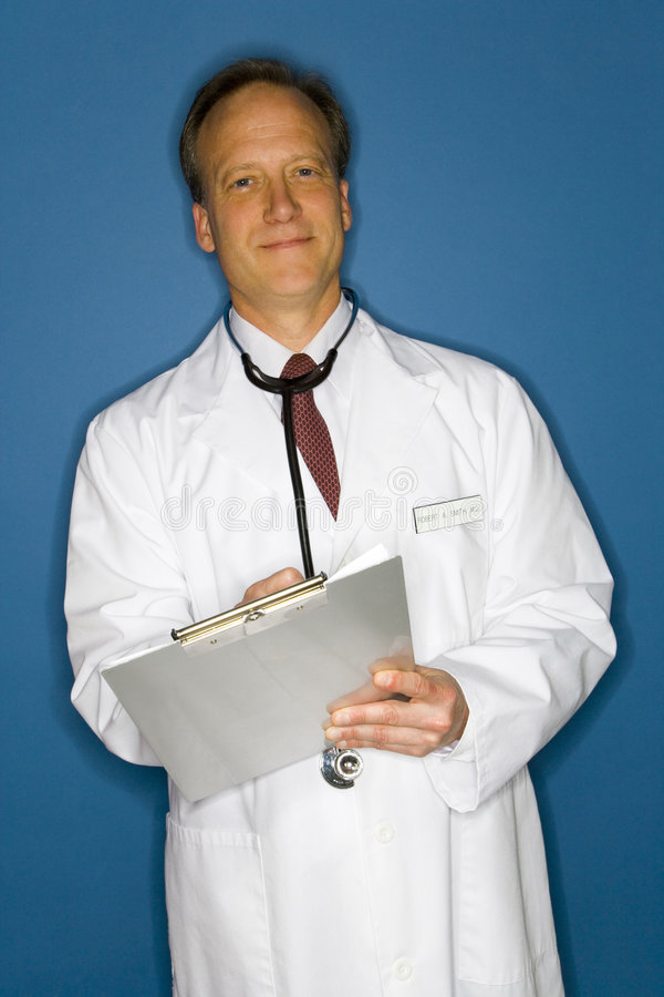 Doctor taking notes. Half body portrait of smiling middle aged doctor in white coat taking notes on clipboard, blue background stock photography