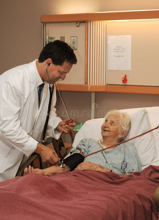 Doctor taking senior blood pressure royalty free stock images