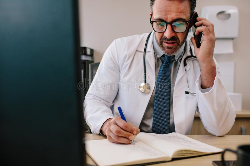 Doctor talking on cell phone and making notes. Mature male doctor talking on cell phone and making notes in his book. Physician making phone call and writing in stock photo
