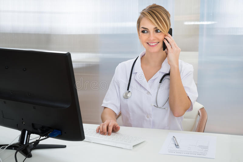 Doctor talking on cellphone. Young Female Doctor Talking On Cellphone While Using Computer stock images