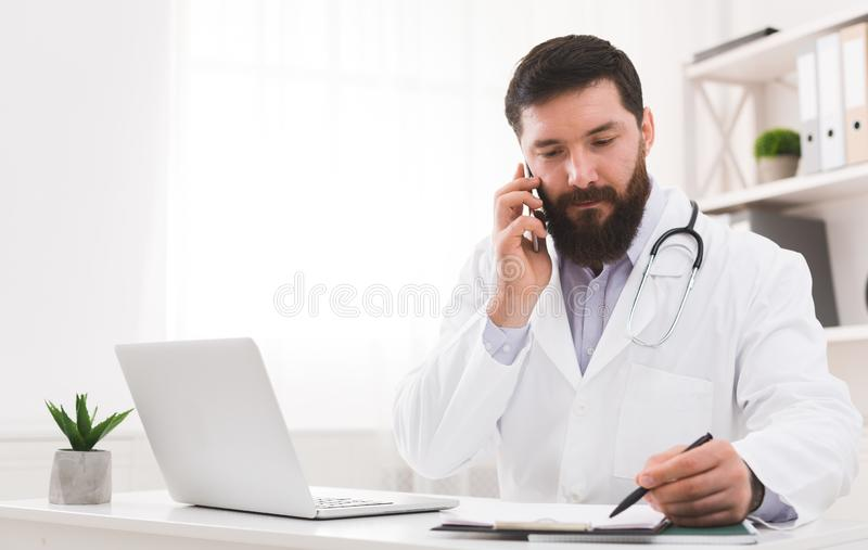 Doctor talking with his patient and writing down diagnosis stock photography