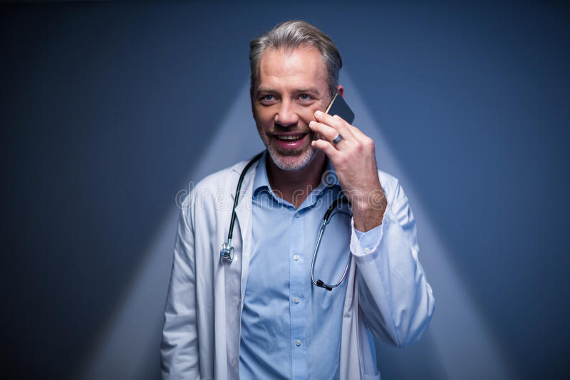 Doctor talking on mobile phone. In hospital royalty free stock photo