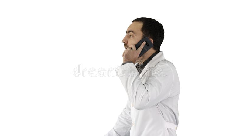 Doctor talking on mobile phone on white background. Medium shot side view. Doctor talking on mobile phone on white background. Professional shot in 4K royalty free stock image