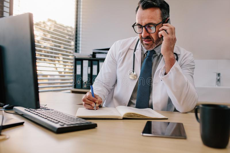 Doctor talking on phone and making notes. Doctor talking over his mobile phone and making notes in a book. Medicine professional talking on phone and writing in royalty free stock photo