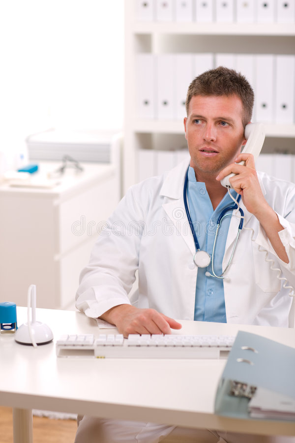 Doctor talking on phone. Medical doctor talking on phone at office stock image