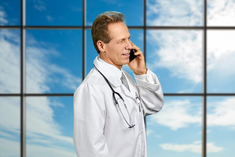 Doctor talking on phone on sky background. Smiling male doctor dressed in white coat talking on his cell phone on clinic window background stock image