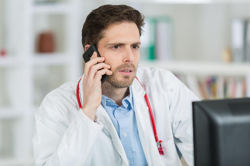 Doctor talking on phone to laboratory for patients results. Doctor talking on the phone to laboratory for patients results stock photo