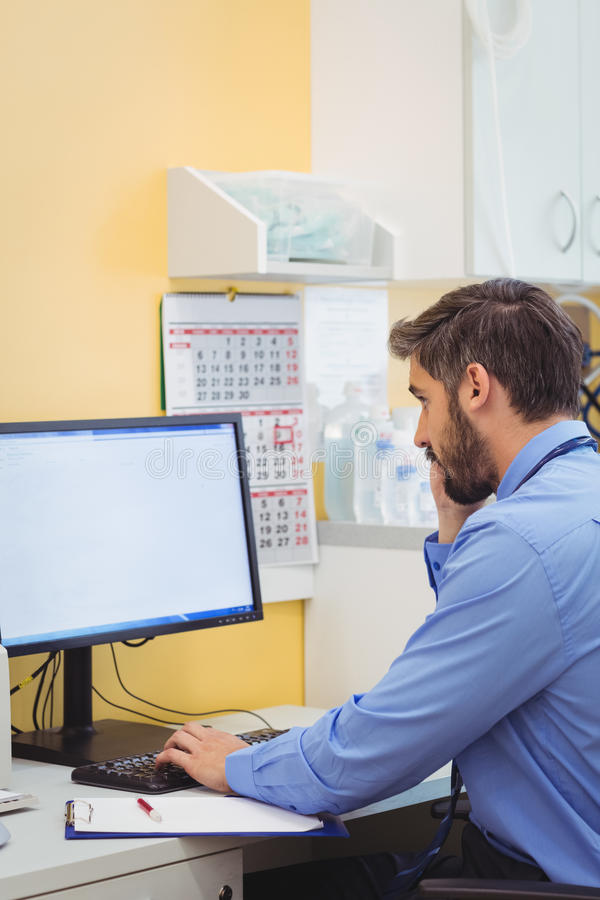 Doctor talking on phone while using computer. At the hospital royalty free stock photos