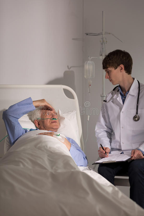 Doctor talking to older patient. Young doctor talking to older patient recovering in hospital royalty free stock photography