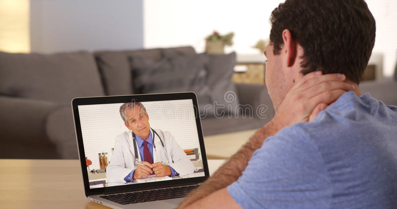 Doctor talking to patient over webcam royalty free stock photos