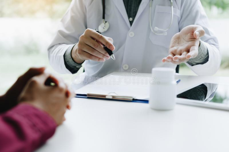 Doctor talking to the patient about suggest the properties of medicines in clinic office.  royalty free stock images
