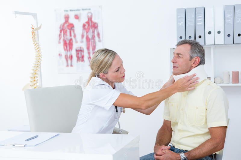 Doctor talking to patient wearing neck brace. In medical office stock photography