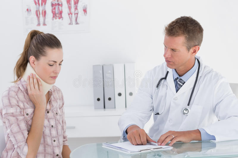 Doctor talking to patient wearing neck brace. In medical office stock photos