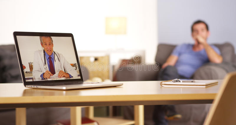 Doctor talking to patient who is texting on his smartphone. Doctor talking to patient who is on his smartphone stock photography