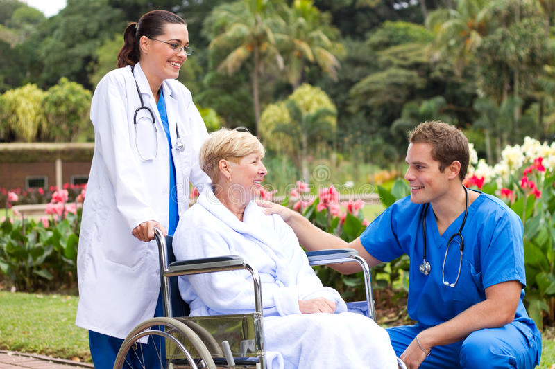 Doctor talking to recovering patient. Young male doctor talking to recovering senior patient outdoors royalty free stock image