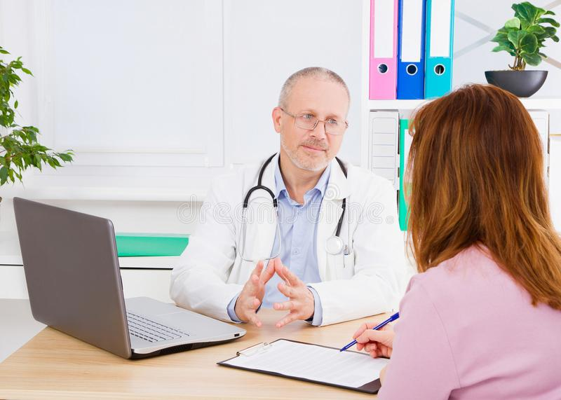 Doctor is talking with woman patient and sitting in medical office.Man in white uniform. Medical insurance. Copy space. Doctor is talking with women patient and royalty free stock photo