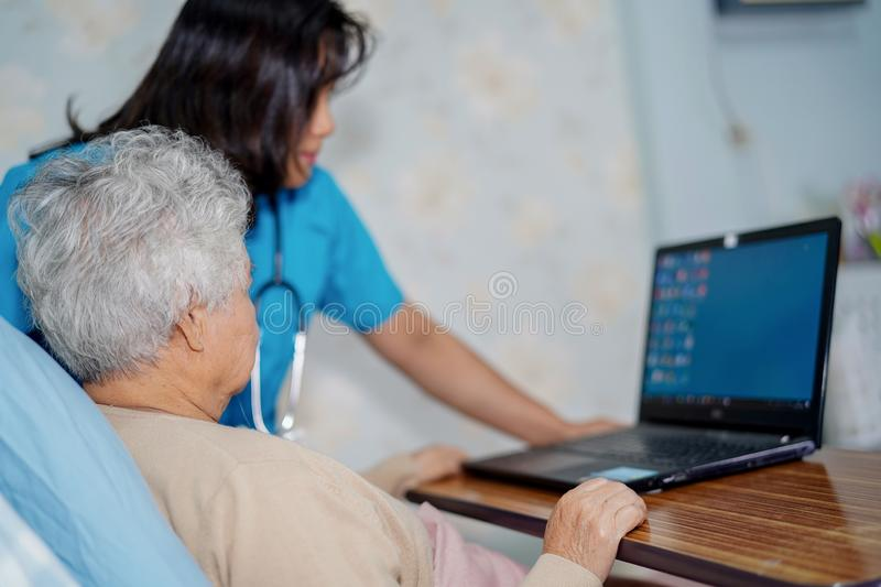 Doctor teach and suggest Asian senior or elderly old lady woman patient to using notebook computer while sitting on bed in nursing stock image