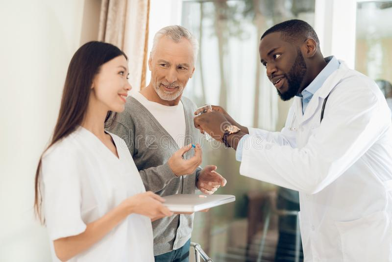 The doctor tells the nurse how an elderly male patient should take pills. The men hears it and he is very focused on the doctor`s words. He is in a nursing stock images