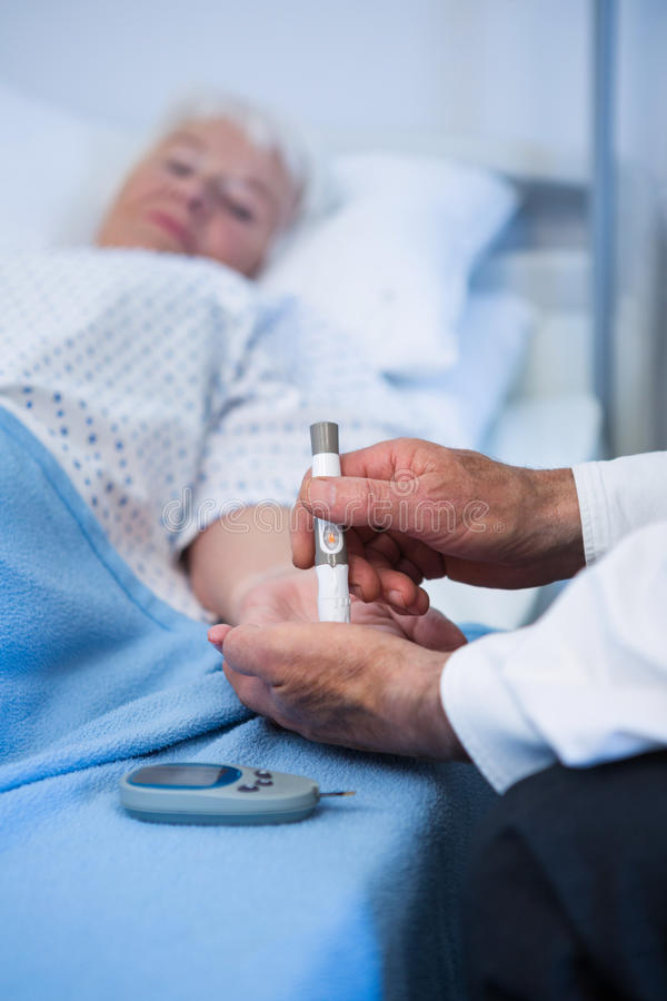 Doctor testing diabetes of senior patient with insulin pen stock image