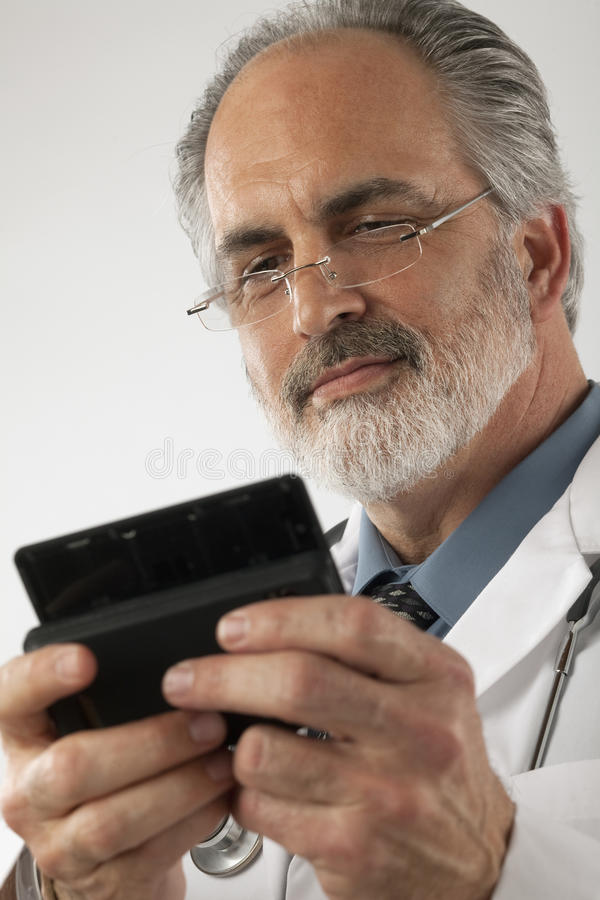 Doctor Texting on a Cell Phone. Close-up of a doctor wearing glasses and a lab coat and texting on a cell phone. Vertical shot royalty free stock photo
