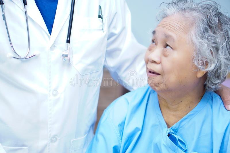 Doctor touching Asian senior or elderly old lady woman patient with love, care, helping, encourage and empathy. Doctor touching Asian senior or elderly old lady royalty free stock photo