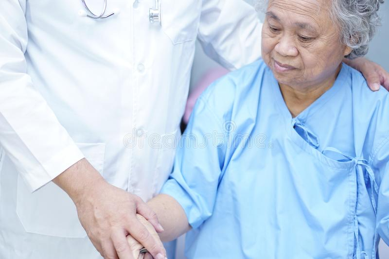 Doctor touching Asian senior or elderly old lady woman patient with love, care, helping, encourage and empathy. Doctor touching Asian senior or elderly old lady royalty free stock images
