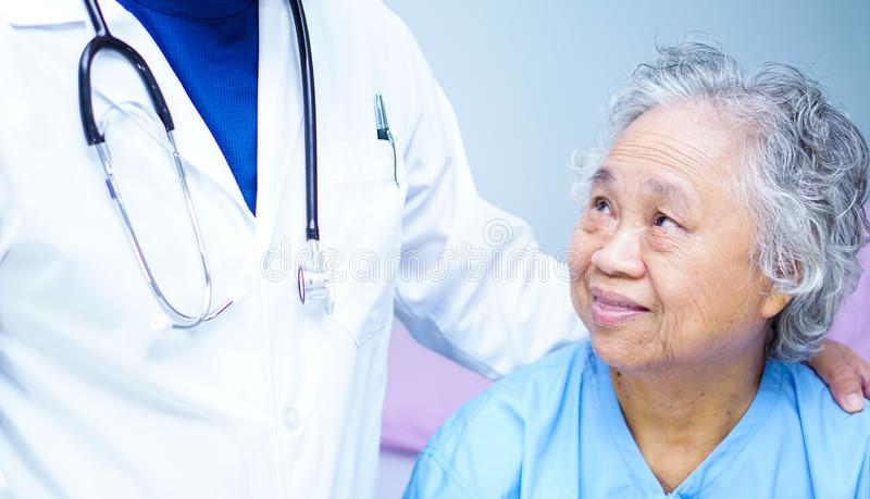Doctor touching Asian senior or elderly old lady woman patient with love, care, helping, encourage and empathy. Doctor touching Asian senior or elderly old lady stock photo