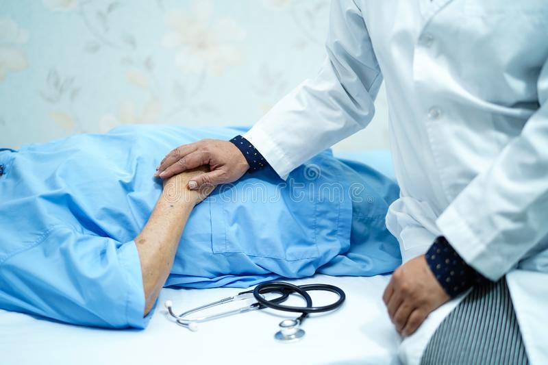 Doctor touching Asian senior or elderly old lady woman patient with love, care, helping, encourage and empathy. Doctor touching Asian senior or elderly old lady stock image