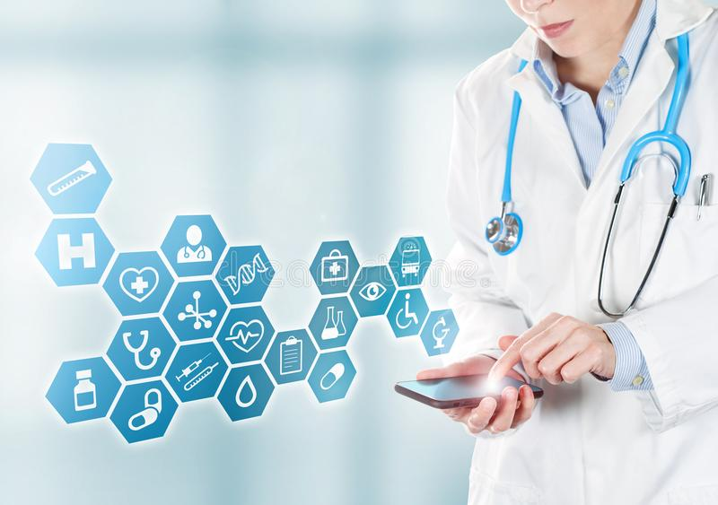 Doctor touching medical buttons on mobile. Female doctor touching a mobile and medical blue icons appearing royalty free stock photos