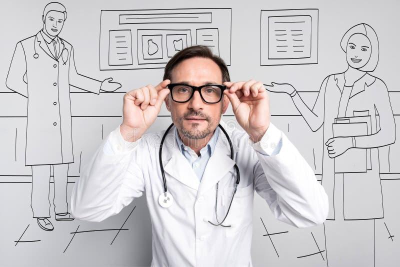 Doctor tranquilo que corrige sus vidrios imágenes de archivo libres de regalías