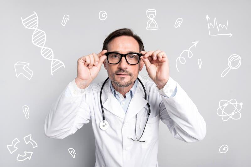 Doctor tranquilo que toca sus vidrios y que parece atento fotos de archivo libres de regalías