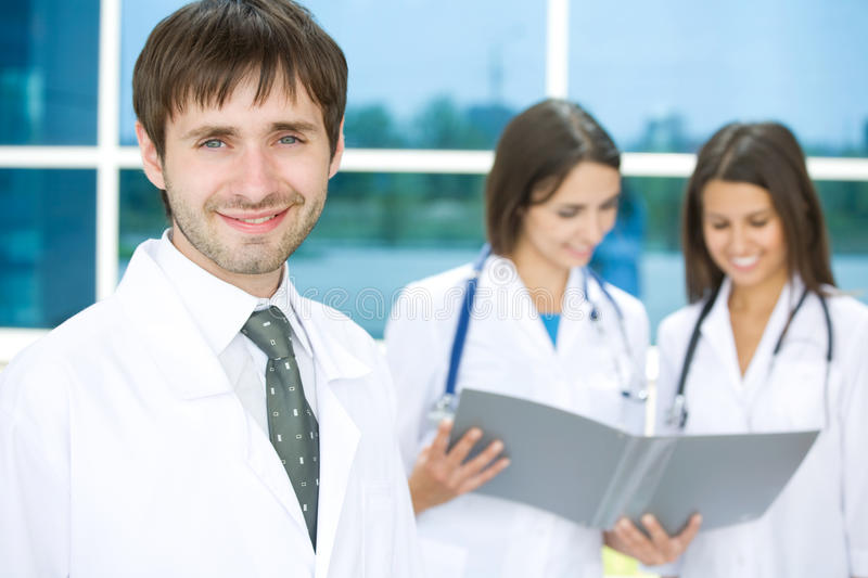 Doctor with two nurses stock images