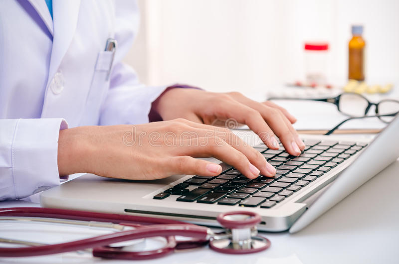 Doctor typing on computer. Doctor typing information on the computer in office royalty free stock images
