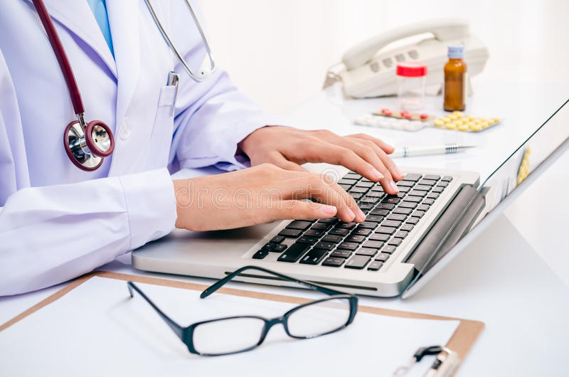 Doctor typing on computer. Doctor typing information on the computer in office stock photography