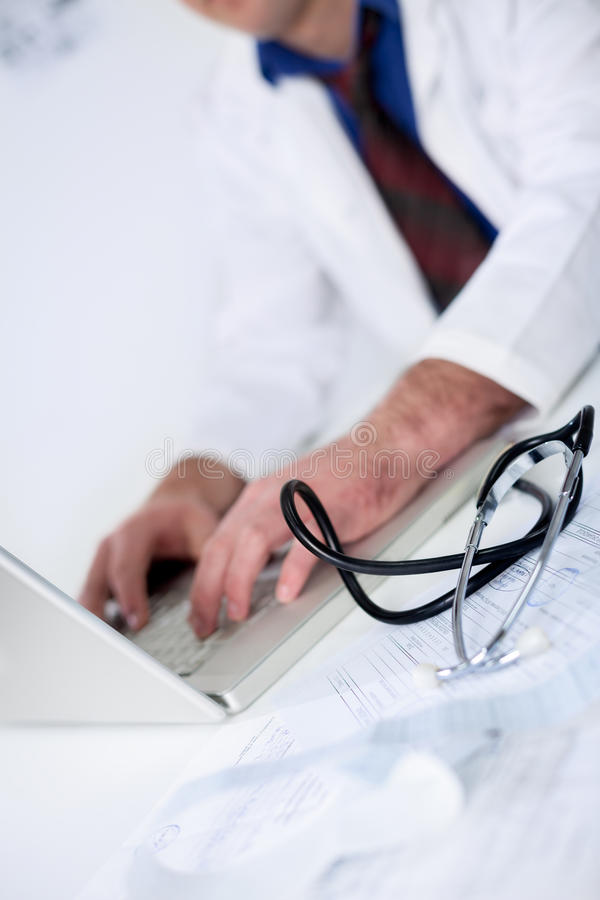Doctor typing on laptop stock images