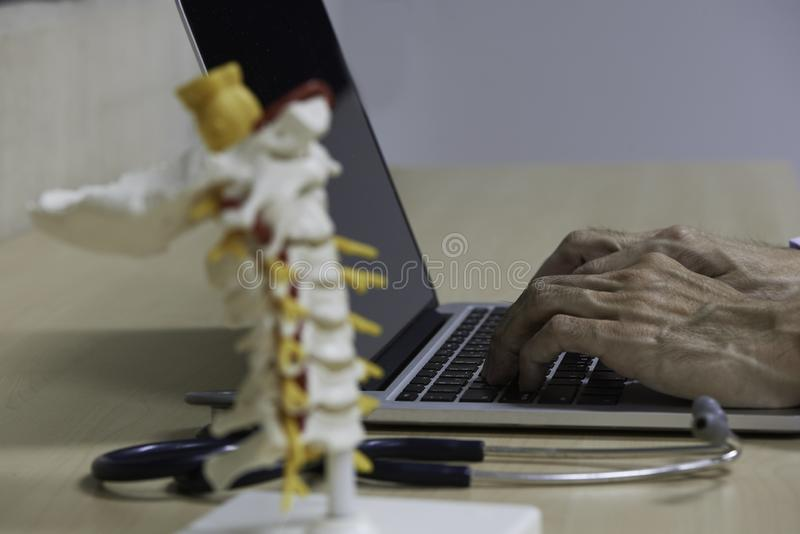Doctor typing laptop computer on the desk royalty free stock photography