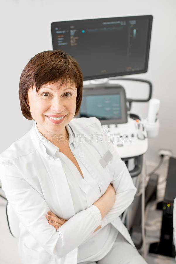 Doctor with ultrasound equipment. Portrait of a senior woman doctor in uniform with ultrasound equipment in the office royalty free stock image