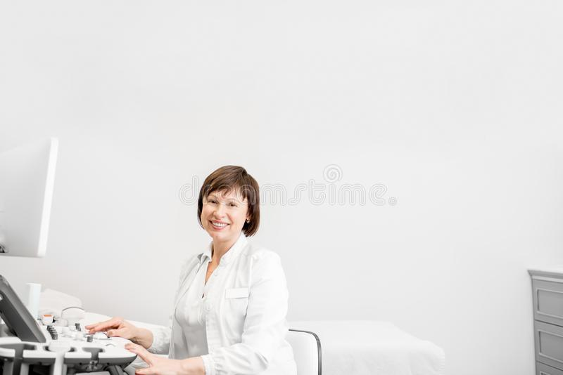 Doctor with ultrasound equipment. Portrait of a senior woman doctor in uniform with ultrasound equipment in the office stock photography